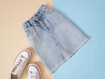Fashionable concept. Female urban style. Denim skirt and white sneakers on a pale blue background. Beige Stock Photography