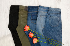 Fashionable concept. Five pairs of jeans of different colors, orange roses. Royalty Free Stock Photography