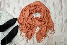 Fashionable concept. Large scarf and black boots. Top view, light wooden background Royalty Free Stock Images