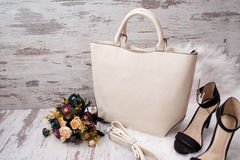 Fashionable concept. Light bag, black shoes and flowers on a white background Stock Photo