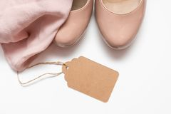 Fashionable concept, pastel beige shoes with high hills and delicate blouse on white background, sale, diascount and shopping royalty free stock image