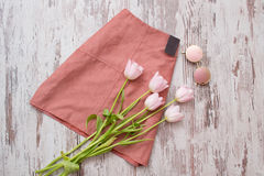Fashionable concept. Pink skirt, glasses and pink tulips. Top view, light wooden background stock images