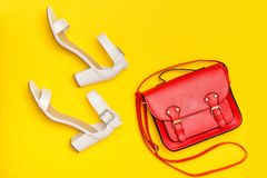 Fashionable concept. Red handbag and white shoes. Yellow background, top view Stock Photo