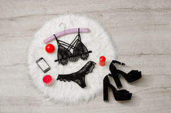 Fashionable concept, a set of lacy underwear, phone, shoes and red candles on the white fur. Top view, Stock Photo
