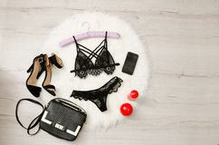 Fashionable concept, a set of lacy underwear, shoes, handbag, phone and red candles on a white fur. top view Royalty Free Stock Images