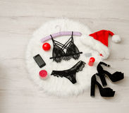 Fashionable concept, a set of lacy underwear, shoes and a red Santa hat, candles, and phone on a white fur Royalty Free Stock Photo