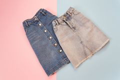 Fashionable concept. Two denim skirts, blue and gray. Tender pink and blue background. Royalty Free Stock Photos