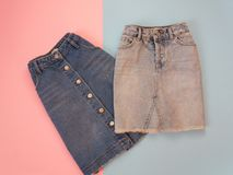 Fashionable concept. Two denim skirts, blue and gray. Tender pink and blue background Royalty Free Stock Photos