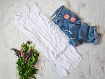 Fashionable concept. White blouse with ties, jeans, glasses and bouquets of flowers Stock Photography