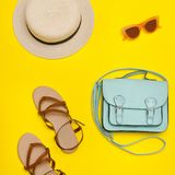 Fashionable concept. Women`s beach hat, handbag, brown shoes. Ye. Llow background. Flat lay Royalty Free Stock Photography