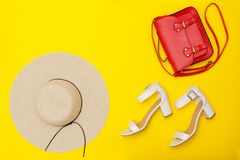 Fashionable concept. Women`s beach hat, red handbag, white shoes. Yellow background, top v Royalty Free Stock Images