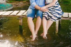 Fashionable cool couple on a bridge near the water, relationships, romance, legs, lifestyle - concept. Fashionable cool couple on a bridge near the water Stock Image