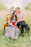 Fashionable cool couple sitting embracing on wooden vintage chair in the garden Royalty Free Stock Images
