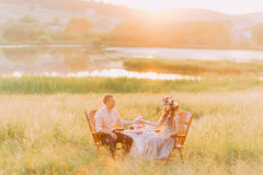 Fashionable cool couple sitting holding hands on vintage chairs in the garden at sunset Stock Images