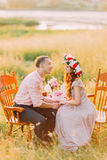 Fashionable cool couple sitting holding hands on vintage chairs in the garden at sunset Royalty Free Stock Photography
