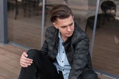 Fashionable cool young man with a trendy hairstyle in stylish clothes relaxes sitting near the modern glass doors. Near the summer cafe outdoors. European guy stock images