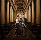 Fashionable couple with automatics Stock Photo