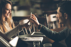 Fashionable couple at the bar using a smart phone Stock Images