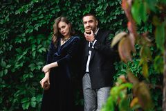 fashionable couple with chocolate doughnuts with green foliage behind looking stock photography