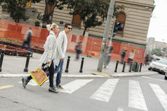 Fashionable couple crossing road at pedestrian zebra crossing Stock Images