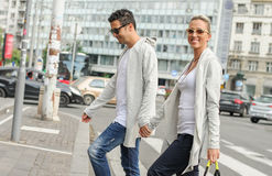 Fashionable couple crossing road at pedestrian zebra crossing Royalty Free Stock Image