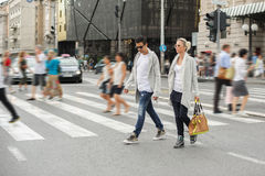 Fashionable couple crossing road at pedestrian zebra crossing Royalty Free Stock Photo