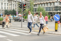 Fashionable couple crossing road at pedestrian zebra crossing Royalty Free Stock Photography