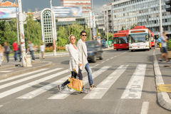 Fashionable couple crossing road at pedestrian zebra crossing Stock Photo