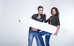 Fashionable couple holding white board Stock Images
