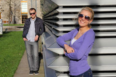 Fashionable couple in park in sunglasses smiling Royalty Free Stock Photo
