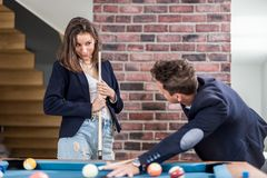 Young modern couple in love playing pool table billiard game. Fashionable couple playing snooker pool table billiard game royalty free stock photo
