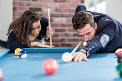 Fashionable couple playing snooker royalty free stock photo
