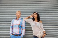 Fashionable couple posing in front of a metal door Stock Photo