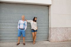 Fashionable couple posing in front of a metal door Royalty Free Stock Photos