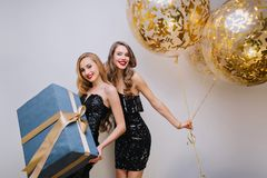 Fashionable curly european girl dancing with balloons behind blonde female friend. Indoor photo of joyful young woman. Fashionable curly european girl dancing royalty free stock photography