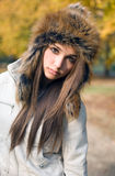 Fashionable cute brunette girl with seriuos look. Fashionable cute brunette girl with serious expresion posing outdoors in the park Stock Images