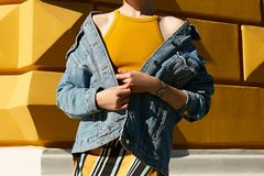 Fashionable denim jacket dropped from the shoulders of a woman i royalty free stock image