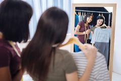 Cheerful women looking at the dress and smiling happily royalty free stock photography