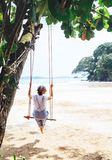 Fashionable dressed Woman sits on tree swing on the wide sandy o Stock Image