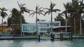 Fashionable estate with glassy walls among palm trees and private pier for mooring boats on sunny isles beach,miami. Magnifincent mansion of wealthy people among stock footage