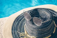 Fashionable expensive sunglasses and designer hat. Women`s accessories at the resort royalty free stock photo