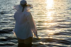 Fashionable fat woman standing in water on sunset Royalty Free Stock Image