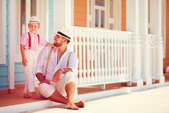 Fashionable father and son sitting and talking on caribbean street Stock Photography