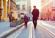 Fashionable father and son walking in old city street Royalty Free Stock Photography