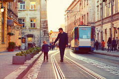 Fashionable father and son walking in old city street Stock Photo