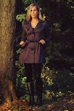 Fashionable female. Blonde in a coat posing near a tree Stock Photo