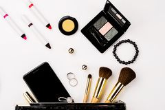 Fashionable female accessories brushes smartphone lipstick eyeshadow and black bag. Overhead of essentials for any girl - Image stock photo