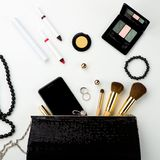 Fashionable female accessories brushes smartphone lipstick eyeshadow and black bag. Overhead of essentials for any girl - Image royalty free stock photography