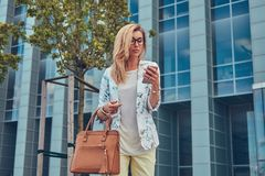 Fashionable female blogger in stylish clothes and glasses with a handbag, holds a smartphone, standing against a Royalty Free Stock Photography