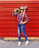 Fashionable female model with skateboard posing on a red wall Stock Image